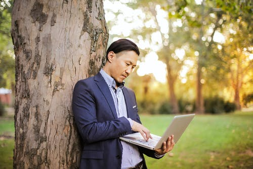 Man wearing Navy Blue Blazer Leaning on Tree Using Laptop