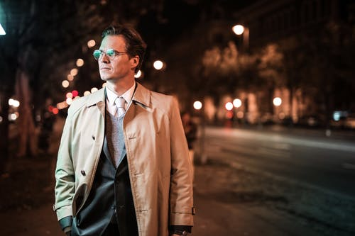 Man in Brown Coat Wearing eyeglasses during Night Time