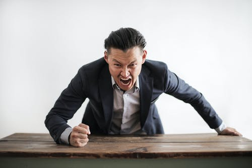 Expressive angry businessman in formal suit looking at camera and screaming with madness while hitting desk with fist