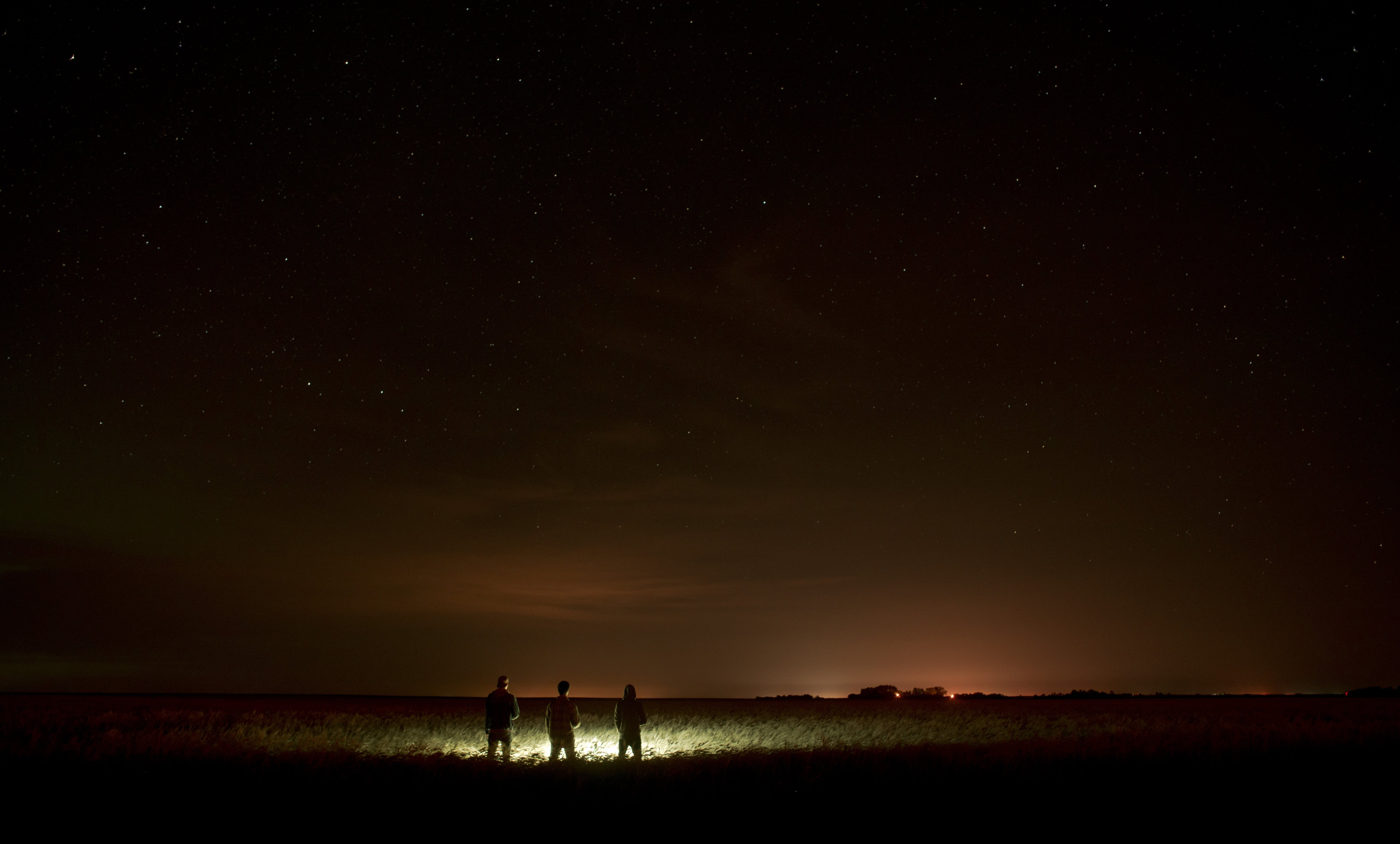 Three People Standing in Front of Lights on Sand during Nighttime