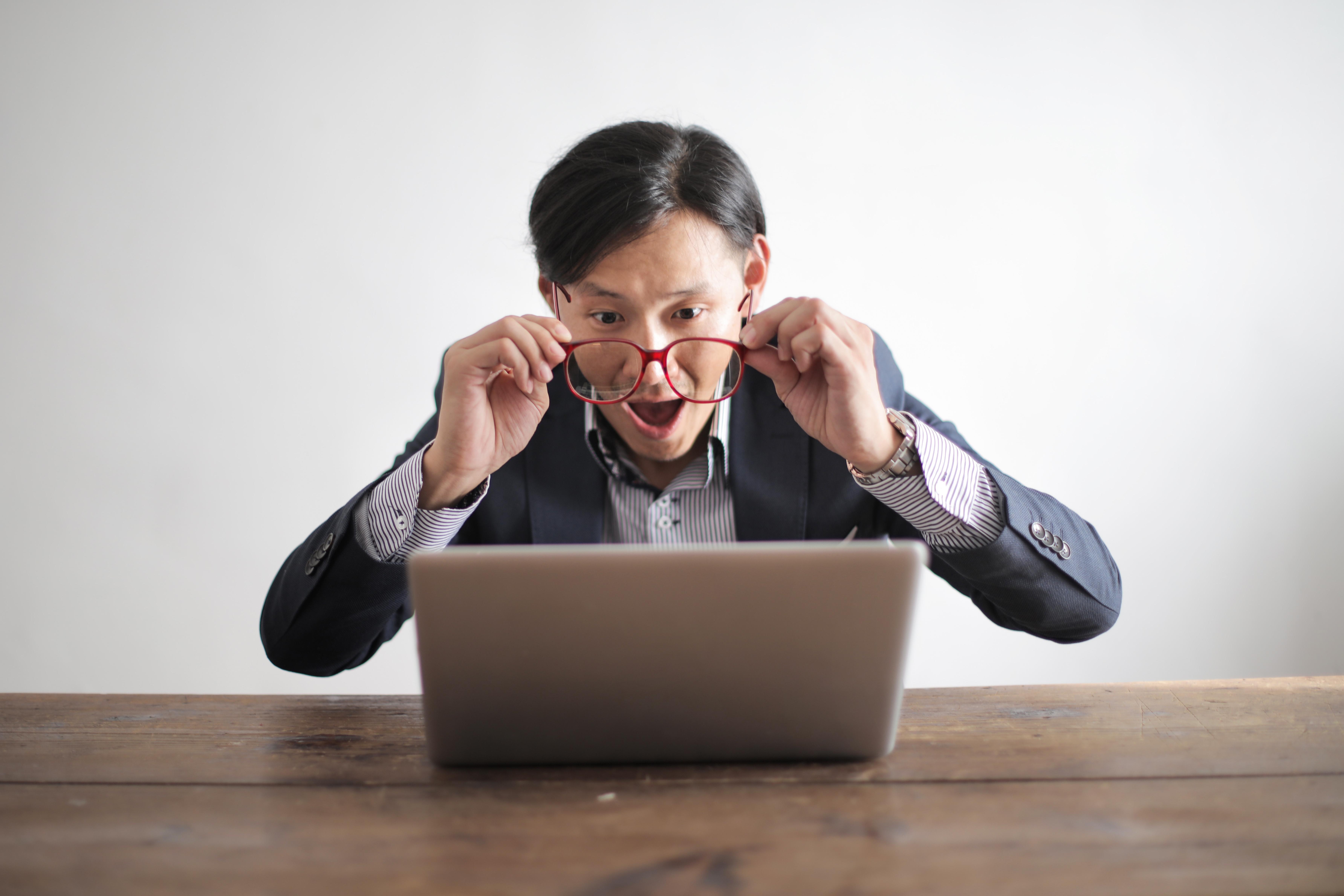 Surprised man looking at laptop.