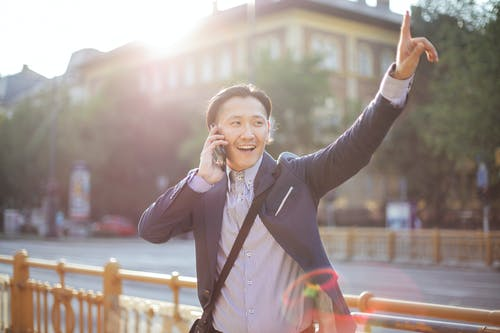 Happy adult ethnic man in jacket waving with hand hailing taxi on sunny street while speaking on smartphone