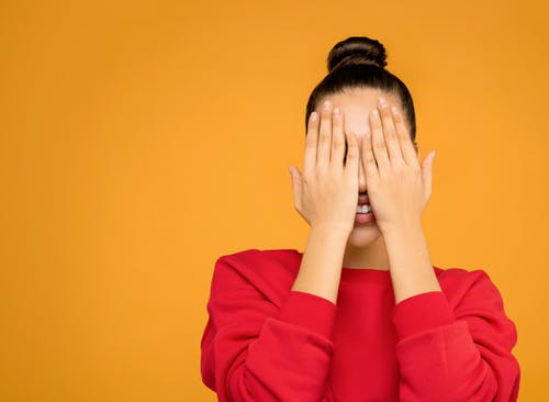 Woman in Red Long Sleeve Shirt Covering Face With Her Hands