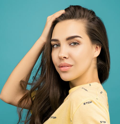Close-up Portrait Photo of Woman in Yellow Top Posing In Front of Blue Background
