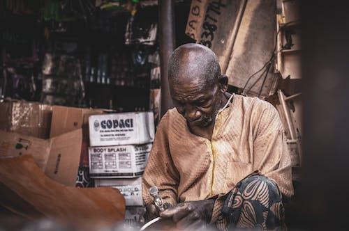 Focused senior black man using hummer in workshop
