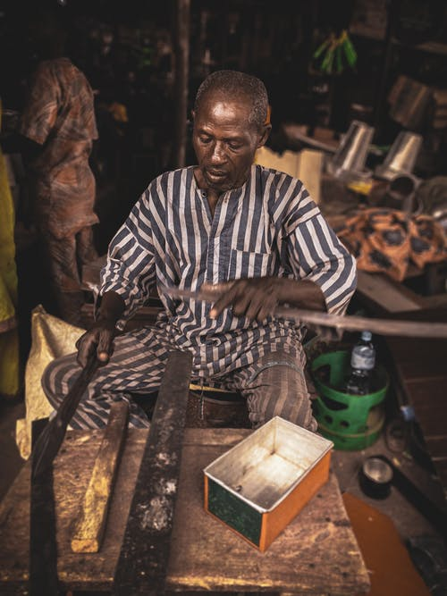 From above of serious middle aged African male artisan in dirty uniform working with metal instruments in old rustic workshop