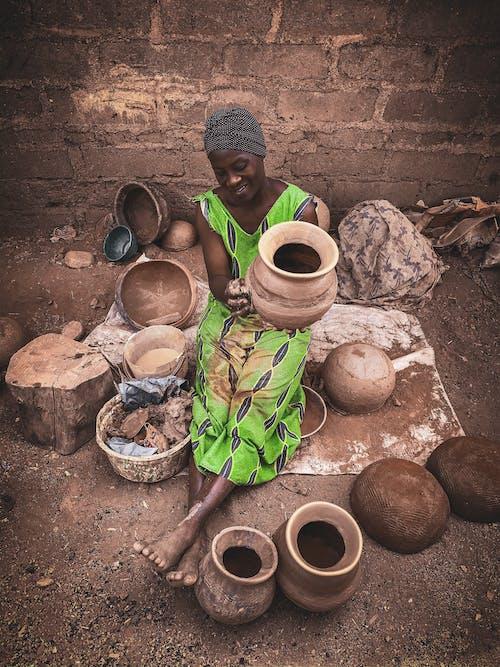 Black woman creating earthenware on street of village