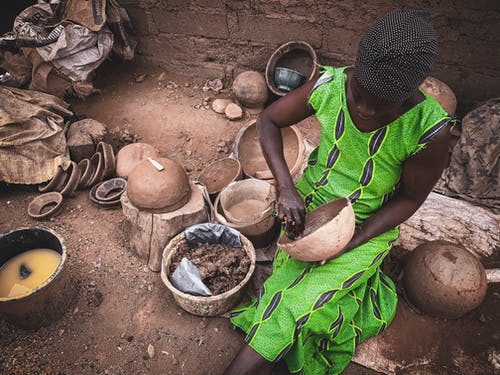 High angle of concentrated African female in light dress sitting on dirty ground of local workshop and creating clay utensils