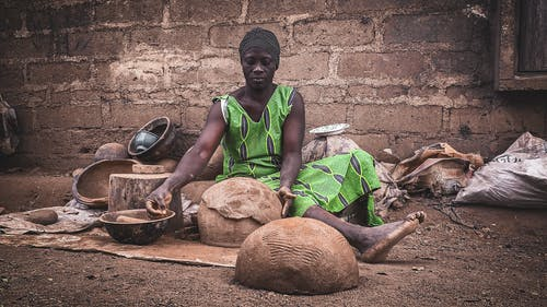 Serious barefooted adult African woman in rustic authentic dress and turban sitting on ground near shabby wall and creating traditional handicraft earthenware