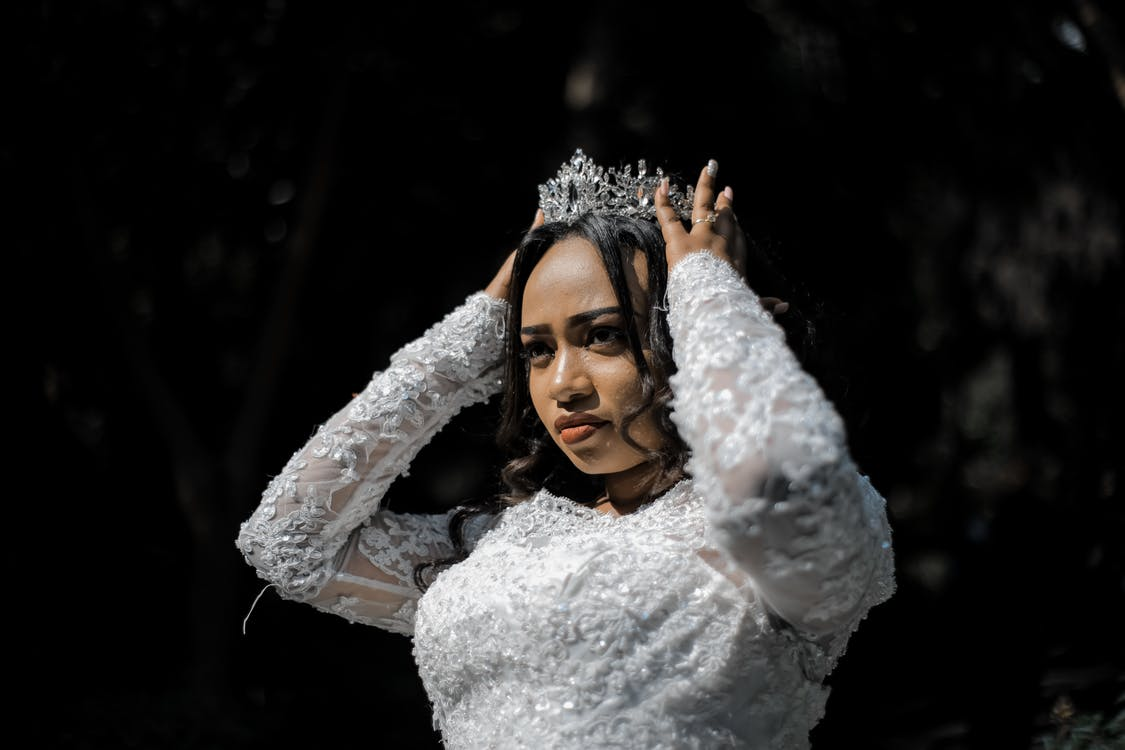 Concentrated ethnic woman in wedding dress and crown before ceremony