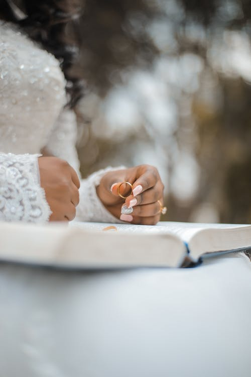 Low angle of crop unrecognizable bride in white dress sitting with book on knees and holding golden ring during wedding ceremony in garden