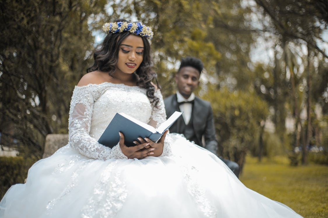 Happy multiethnic newlywed couple with Holy Bible in garden during wedding celebration