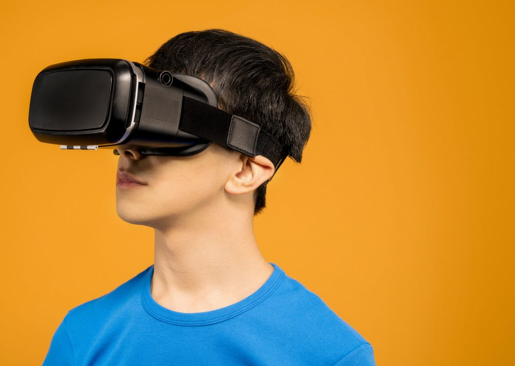Man in Blue Crew Neck Shirt Wearing Black VR Headset