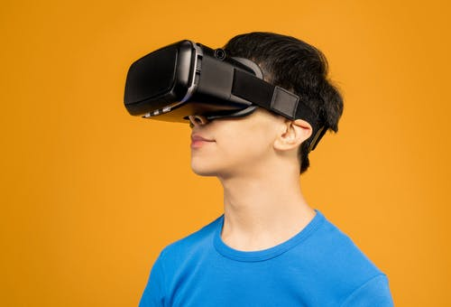 Man in Blue Crew Neck Shirt Wearing Black VR Headset