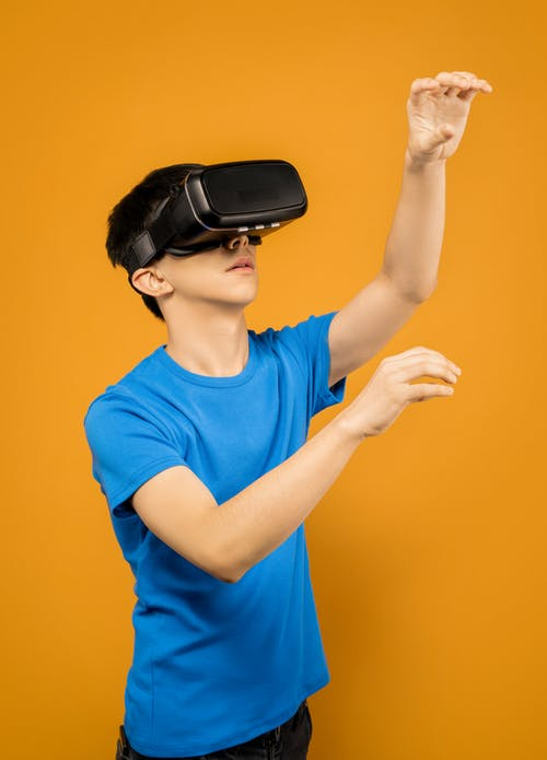 Man in Blue Crew Neck T-shirt Wearing Black VR Goggles