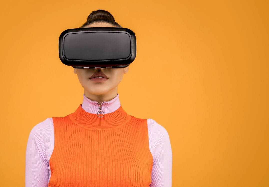 Woman in Orange and Pink Shirt Wearing Black VR Headset