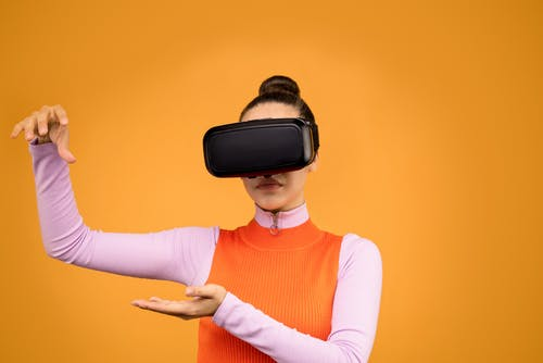 Woman in Pink and Orange Long Sleeve Shirt Wearing Black VR Goggles