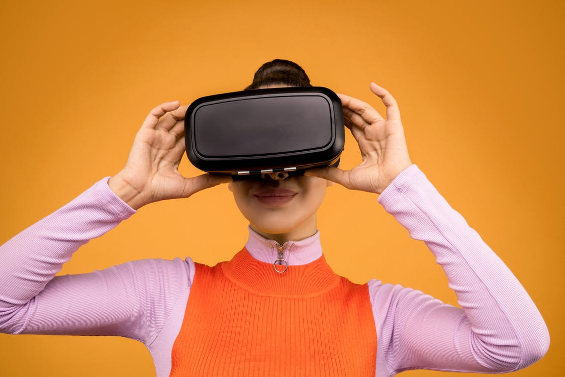 Woman in Orange and Pink Long Sleeve Shirt Holding Black and Gray Vr Gadget