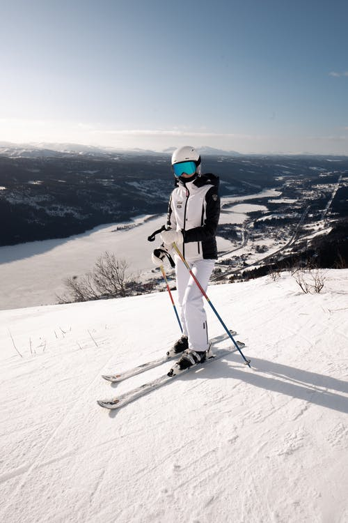 Person in White Jacket and White Pants Riding Ski Blades on Snow Covered Mountain
