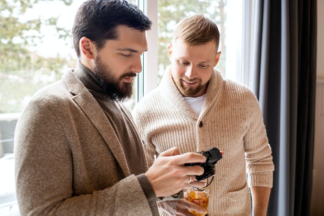 Man in Brown Sweater Holding Black Dslr Camera