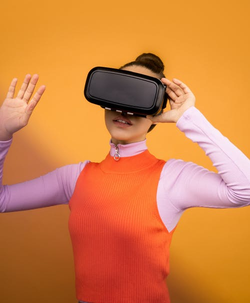 Woman in Long Sleeve Shirt Holding VR Headset