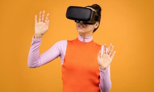 Woman in Orange and Pink Long Sleeve Shirt Wearing Black Virtual Reality Gadget