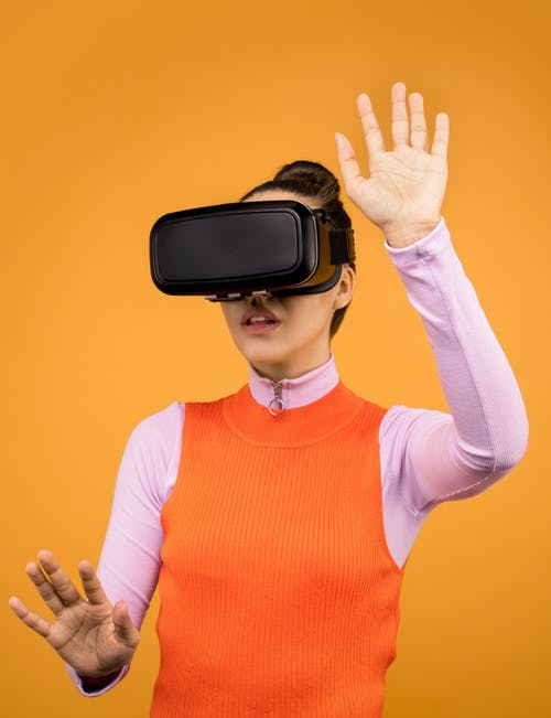 Woman in Orange and Pink Long Sleeve Shirt Wearing Black Vr Goggles