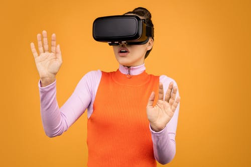 Woman in Long Sleeve Shirt Wearing VR Goggles
