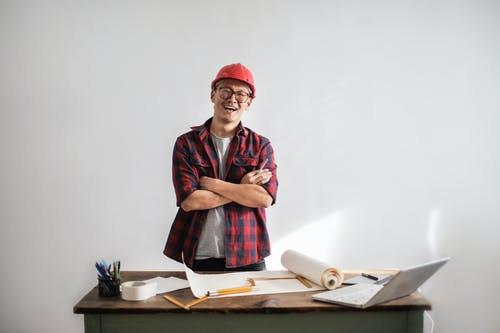 Smiling casual man in hardhat and glasses holding arms crossed looking at camera while standing at desk with paper draft and stationery