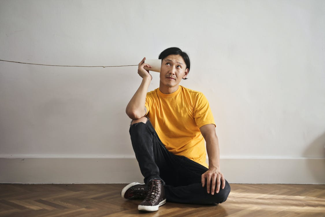 Asian guy in casual clothes using paper cup with thread as telephone while sitting on floor against white wall