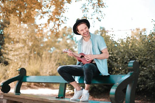 Man Sitting on Wooden Bench Using Ukulele