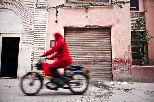 Woman in Red Coat Using Bicycle
