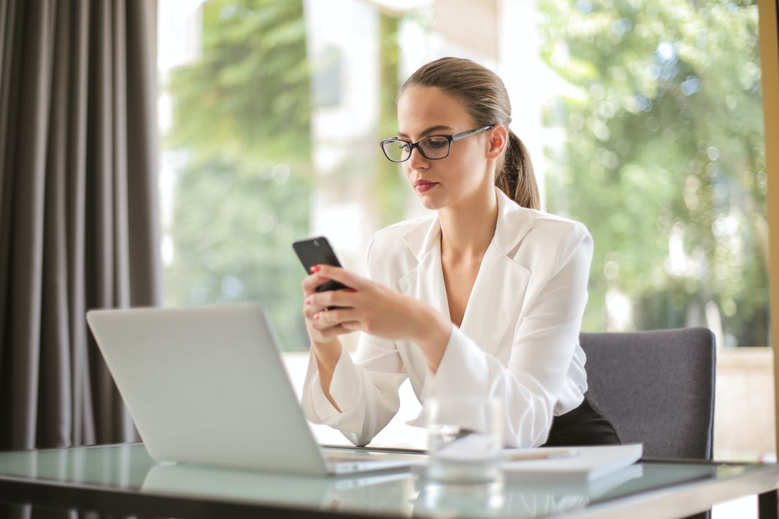 Concentrated young woman in formal clothes and eyeglasses sitting at glass table with laptop while surfing smartphone