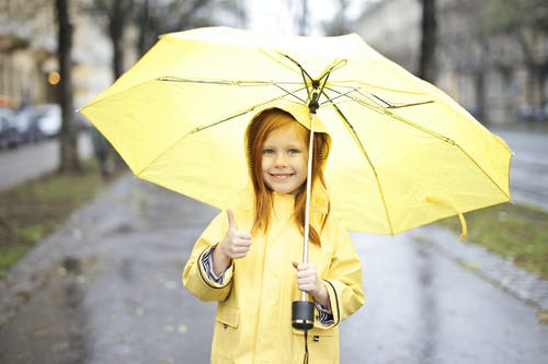 Photo of Smiling Girl in Yellow Raincoat Holding a Yellow Umbrella While Giving One Thumbs Up
