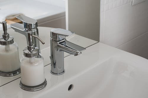 Close-up Photo of White Ceramic Sink With Stainless Steel Faucet