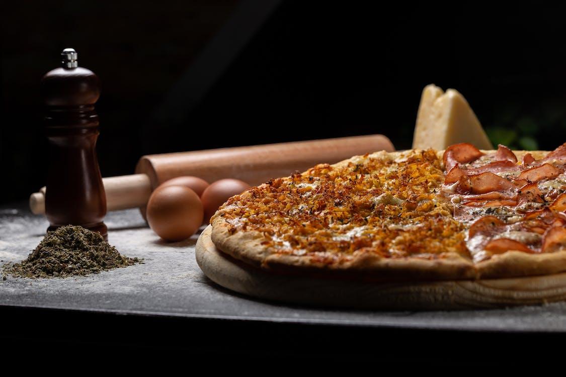 卵と麺棒の横にある木の板のピザ