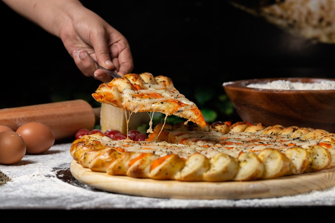 Person Holding Pizza on Wooden board