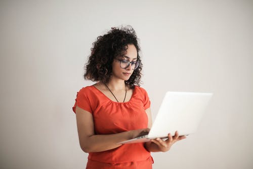 Photo of a Woman in an Orange Top Using a Laptop While Standing