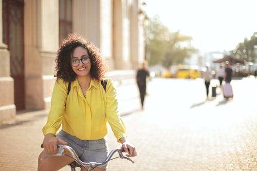 Selective Focus Photo of Smiling White Woman in Yellow Top Sitting on a Bicycle