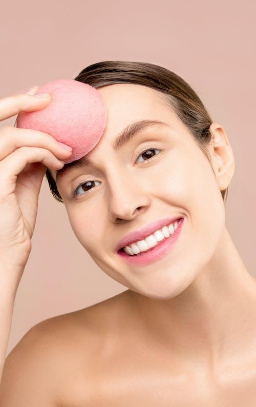 A Woman Using A Makeup Sponge Blender