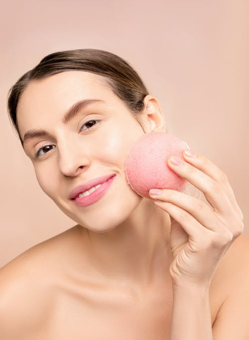 Woman Holding Pink Round Sponge