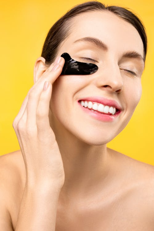 Woman With Black Under Eye Mask Smiling