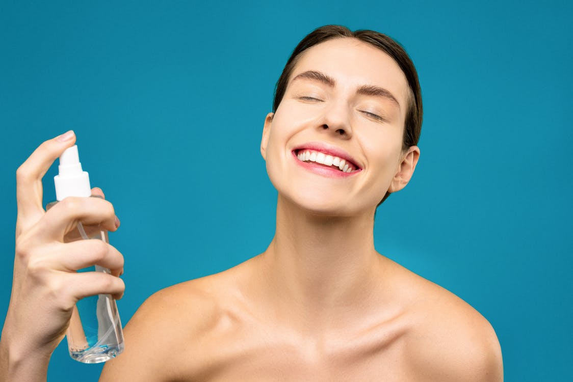 Smiling Woman Holding Clear Spray Bottle