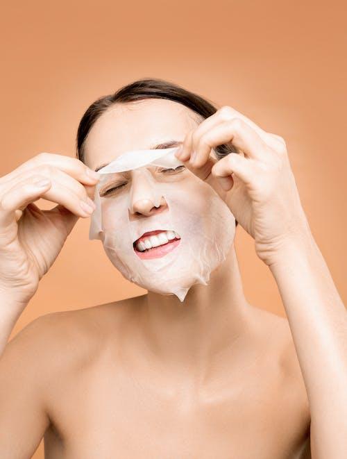 Frau, Die Weiße Gesichtsmaske Entfernt