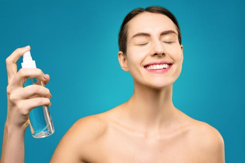 Smiling Topless Woman Holding Clear Glass Bottle