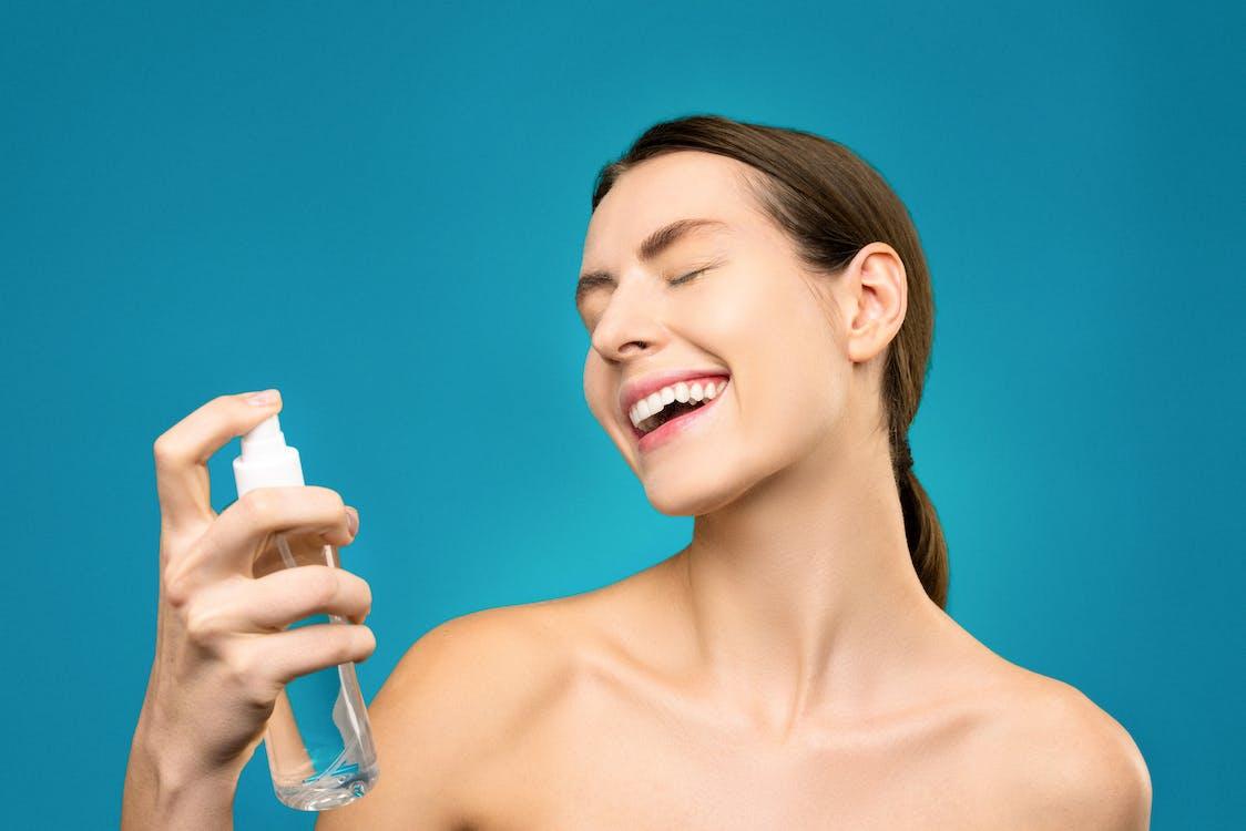 透明なガラス瓶を保持している女性