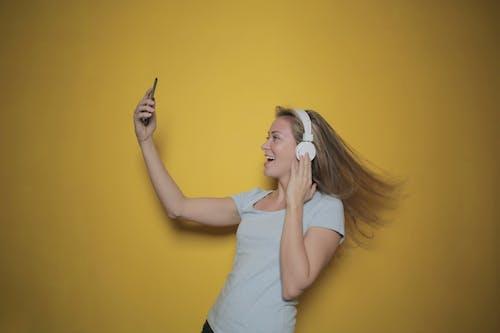 Kostenloses Stock Foto zu blond, festhalten, frau, gelbem hintergrund