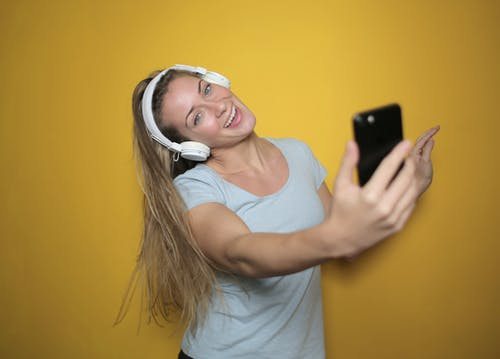 Photo of Smiling Woman in White Tank Top Listening to Music on Headphones While Taking a Selfie