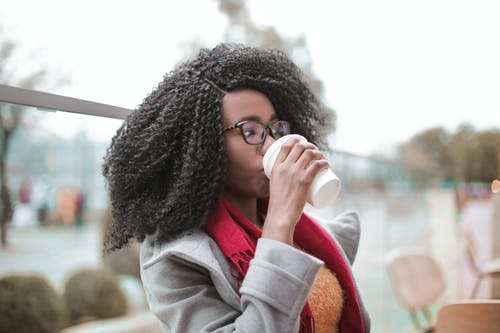 Selective Focus Photo of Woman in Gray Coat Drinking Coffee
