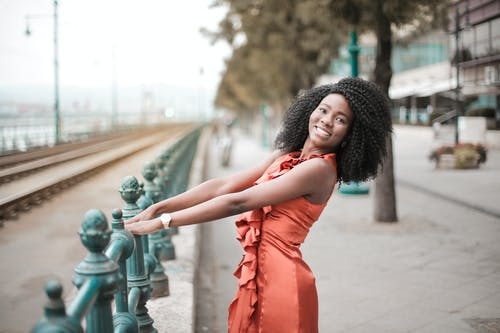 Photo of Smiling Woman in Orange Dress Posing By Metal  Railing